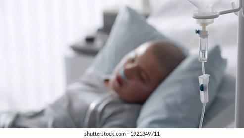 Focus on intravenous drip with sick kid lying in hospital bed on background. Teen boy patient with cancer resting in bed having medication in dropper