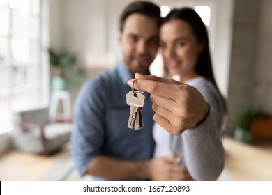 Focus on keys, held by excited young spouses homeowners. Happy married family couple celebrating moving in new house home , demonstrating keys, standing in apartment, real estate mortgage concept.