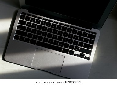 Focus on laptop keyboard with sunlight shine on