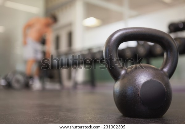 Focus on large black kettlebell in weights room at the gym