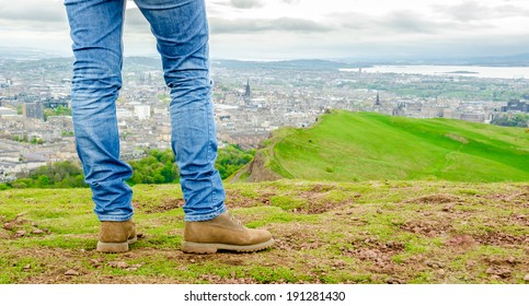 Focus on legs of a female model wearing skinny blue jeans and brown suede boots admiring Edinburgh landscape from the top of the Arthur's seat. Scotland, UK.