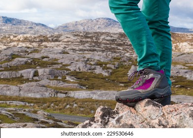 Focus on legs of a female model wearing purple and grey hiking boots with rocky landscape in the background. Scotland, UK.