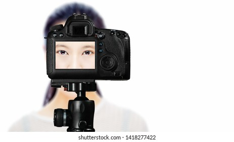 Focus on live view on camera on tripod, teenage girl  beauty shoot image on back screen with blurred scene in background. Teenage vlogger livestreaming show concept