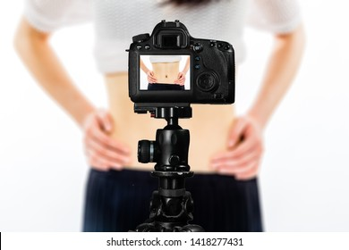 Focus on live view on camera on tripod, teenage girl  showing waistline from diet image on back screen with blurred scene in background. Teenage vlogger livestreaming show concept