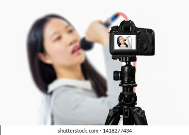 Focus on live view on camera on tripod, teenage girl  singing with microphone image on back screen with blurred scene in background. Teenage vlogger livestreaming show concept