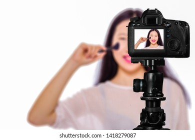 Focus on live view on camera on tripod, teenage girl  using cosmetics image on back screen with blurred scene in background. Teenage vlogger livestreaming show concept