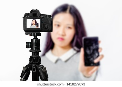 Focus on live view on camera on tripod, teenage girl  holds cracked phone image on back screen with blurred scene in background. Teenage vlogger livestreaming show concept