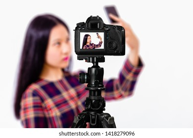Focus on live view on camera on tripod, teenage girl  taking selfie image on back screen with blurred scene in background. Teenage vlogger livestreaming show concept