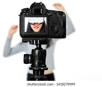 Focus on live view on camera on tripod, teenage girl  using VR goggles image on back screen with blurred scene in background. Teenage vlogger livestreaming show concept
