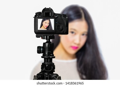 Focus on live view on camera on tripod, teenage girl  makeup beauty shoot image on back screen with blurred scene in background. Teenage vlogger livestreaming show concept