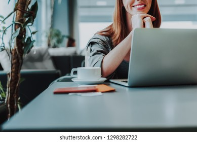 Focus on low angle of cheerful woman sitting at table with cup of hot drink. She is exploiting laptop during her leisure