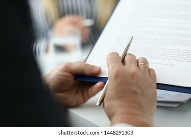 Focus on male hand holding pen and paper folder with contract. Partner checking conditions of important biz bargain in meeting room. Blurred background