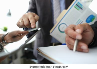 Focus on male hand pointing at tablet screen and explaining something. Colleagues holding important documents with biz charts, graphs, diagrams. Business meeting concept. Blurred background