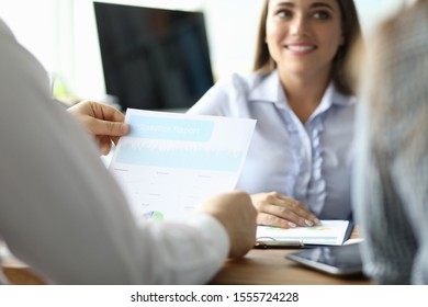 Focus on male hands holding important business documents. Man and woman sitting at table and discussing statistics report of new project. Teamwork concept