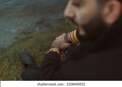 Focus on male hands over the shoulder of a seated person. A thoughtful, melancholy pose.