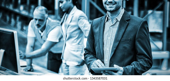 Focus on manager is smiling and holding a tablet in front of his colleagues in a warehouse