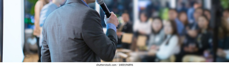 Focus on microphone held by panel speaker on stage during presentation. Executive manager presenter at corporate conference talking to audience.  Business leadership CEO lecture during seminar.
