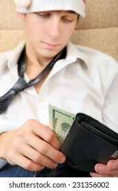 Focus on Money. Teenager in Santa Hat Checking the Wallet on the Sofa at the Home