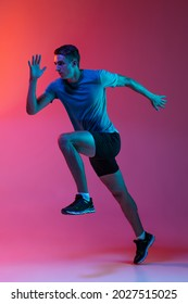 Focus on movement. Portrat of professional male athlete, runner training isolated on pink studio background with blue neon filter, light. Concept of action, motion, speed, healthy lifestyle. Copyspace - Shutterstock ID 2027515025