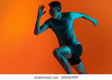 Focus on movement. Portrat of professional male athlete, runner training isolated on orange studio background with blue neon filter, light. Concept of action, motion, speed, healthy lifestyle - Shutterstock ID 2033347859