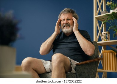 Focus on only one. Old bearded man in black shirt sitting on the chair and suffering from migraine on blue background. Concept of illness, diseases of the neurology system, CNS pathology, healthcare.