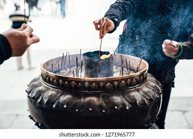focus on people hands holding incense sticks light up by fire in the middle of large burner at todaiji nara japan. local people praying blseeing doing traditional religion process in japanese temple.