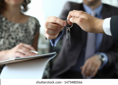 Focus on people hands holding key of expensive apartment. Businessman in classy suit giving brunch to man and woman signing contract. Biz meeting concept. Blurred background