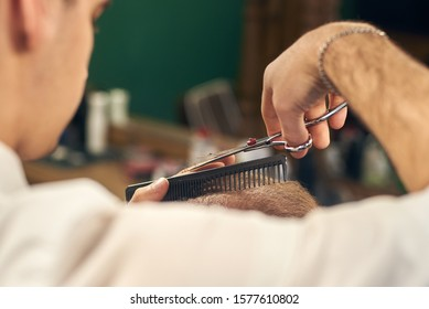 Focus on professional hairdressing scissors during process of trimming of ends on short men's hair. Application of traditional methods for servicing clients in modern barbershop. Detailed macro view.