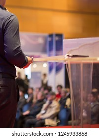 Focus on Remote Control and Hand of Presenter on Stage. Speaker Behind Podium in front of Audience at Conference Presentation. Attendees at Investor Event Hearing Investor Pitch at Seminar Meeting
