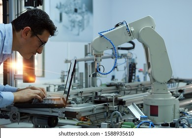 Focus on robotic arm. Engineer is working on laptop to programming  smart factory automation and automated car on production line. Industry 4.0 concept; artificial intelligence in smart factory.