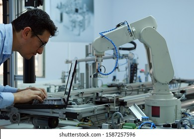 Focus on robotic arm which picks up product from automated car on production line and an engineer working on laptop to programming. Industry 4.0 concept; artificial intelligence in smart factory.