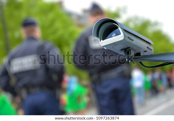 Focus on security CCTV camera or surveillance system with police officers on blurry background