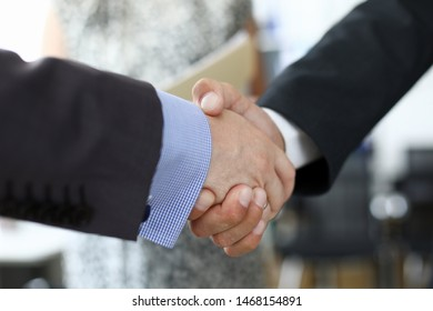 Focus on shake hands of two businessmen performing gesture of mutual agreement in complicated and important business meeting. Biz concept. Blurred background