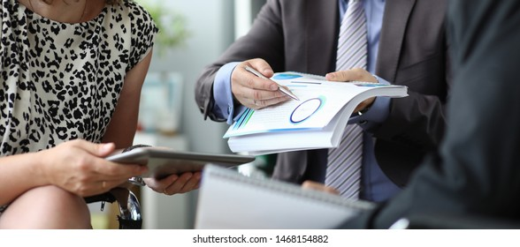 Focus on smart businessman pointing at biz statistics. Businesspeople sitting in corporation conference room and discussing new start-up. Business meeting concept. Blurred background