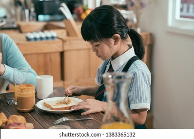 focus on smart cute little girl having breakfast wear uniform before school in morning. daughter sitting beside mom putting peanut jam on bread toast. family time healthy lifestyle early day.