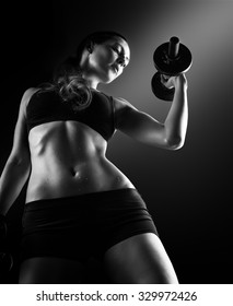 Focus on stomach. Black and white dark contrast portrait of young beautiful fitness woman with beads of sweat which training in gym. Working out with dumbbells on black background