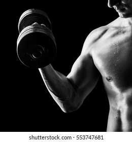 Focus on stomach. Black and white contrast shot of young muscular fitness man chest and arm. Bodybuilder with beads of sweat training in gym. Working out with dumbbells on black background