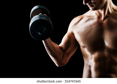 Focus on stomach. Dark contrast shot of young muscular fitness man stomach and arm. Bodybuilder with beads of sweat training in gym. Working out with dumbbells on black background