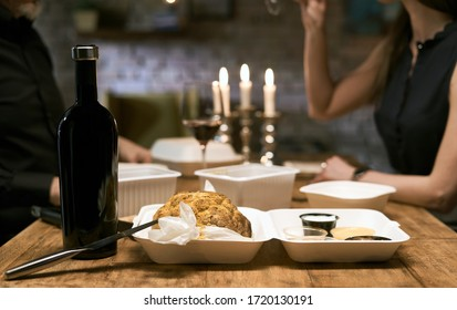 Focus on takeaway delivery food. Couple having dinner at home, drinking wine in the background. Ordered food delivery, eating and people concept.