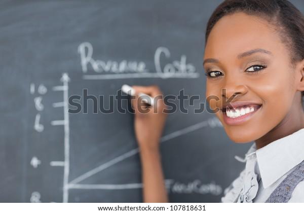 Focus on a teacher drawing a chart on a blackboard in a classroom
