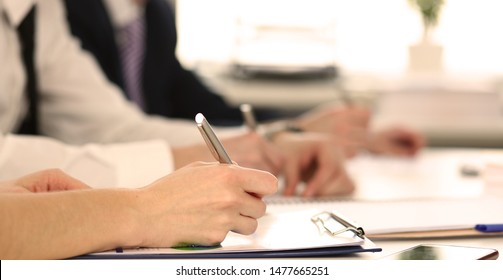 Focus on tender female hand holding pen. Directors signing biz documents discussing stipulation of contract and closing bargain. Business meeting concept