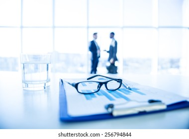 Focus on the things on the table. Blurred men near panoramic windows on background.