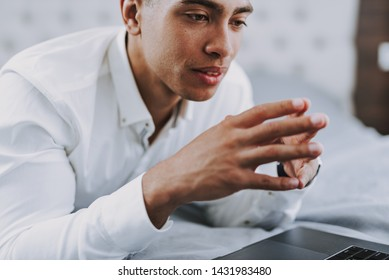 Focus on thoughtful young man in elegant white shirt lying on bed. He is looking at notebook screen