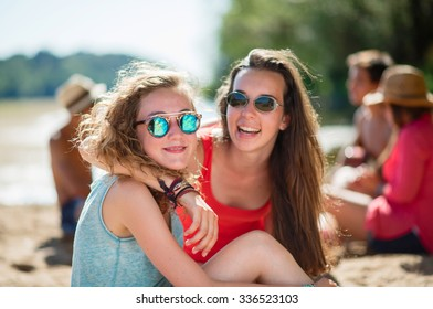 Focus on two trendy young girls sitting close with their friends in the sand on a river side. They are having fun, smiling and looking at camera, wearing summer tops and sunglasses.