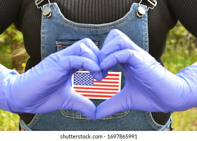 Focus on US flag batch on a jeans jumper with woman's hands in gloves making love gesture