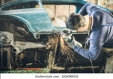 Focus on vintage car body - Man mechanical worker repairing with electric grider in messy garage - Work safety with protection wear - Niche expertise concept with guy working with technical equipment