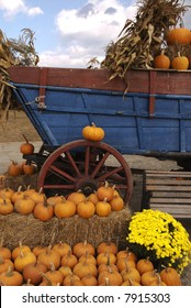 Focus is on the wagon wheel surrounded by pumpkins
