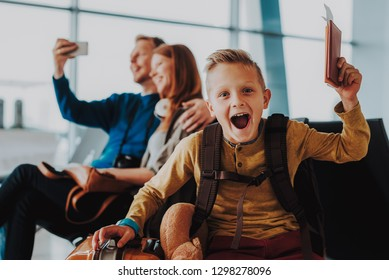 Focus on waist up portrait of excited kid while opening mouth with joy. He is sitting near suitcase and lifting up hand with tickets. His parents are taking photo of themselves on background
