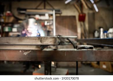 Der Fokus liegt auf der Schweißleitung, und dahinter liegt der Arbeiter, der die Rohre in der alten Werkstatt schweißt.