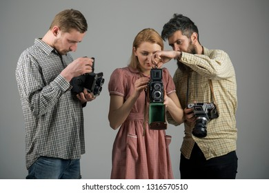 Focus on what matters. Paparazzi or photojournalists with vintage old cameras. Group of photographers with retro cameras. Retro style woman and men hold analog photo cameras. Photography studio.